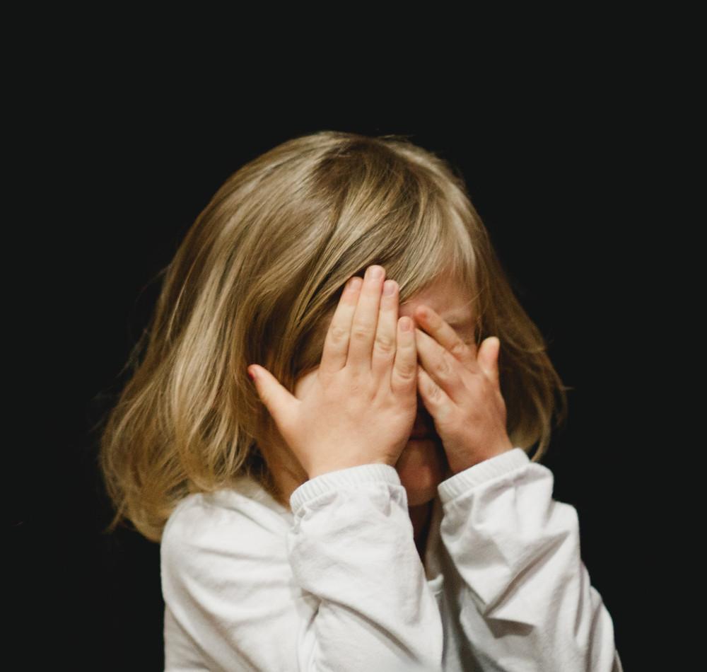 Little girl hiding behind her hands