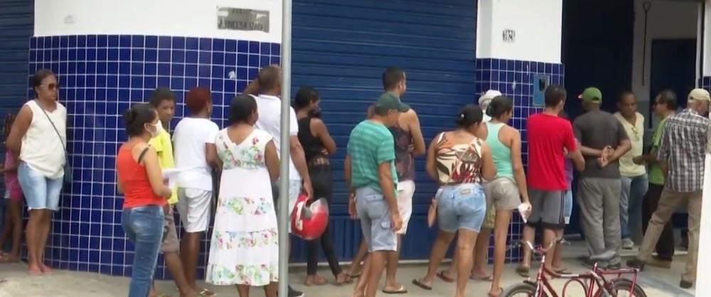 Diversas pessoas próximas umas das outras no lado de fora de uma lotérica, próximas a uma parede em uma fila que dobra a esquina.