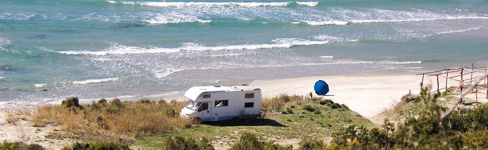 White caravan vehicle parked on a beach