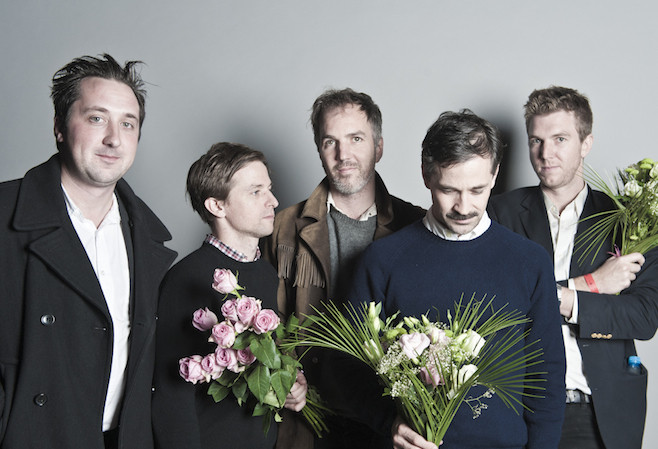 Members of the Walkmen holding floral bouquets