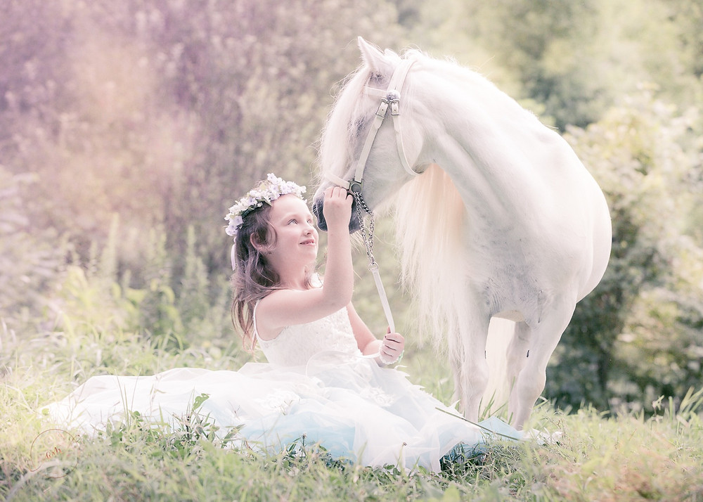 fairytale princess with white pony during equine photo shoot