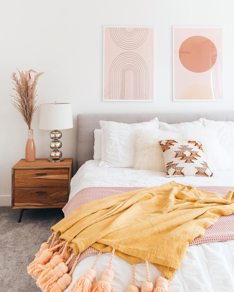 A boho master bedroom with a yellow tassel blanket on the end of the bed and blush accents.
