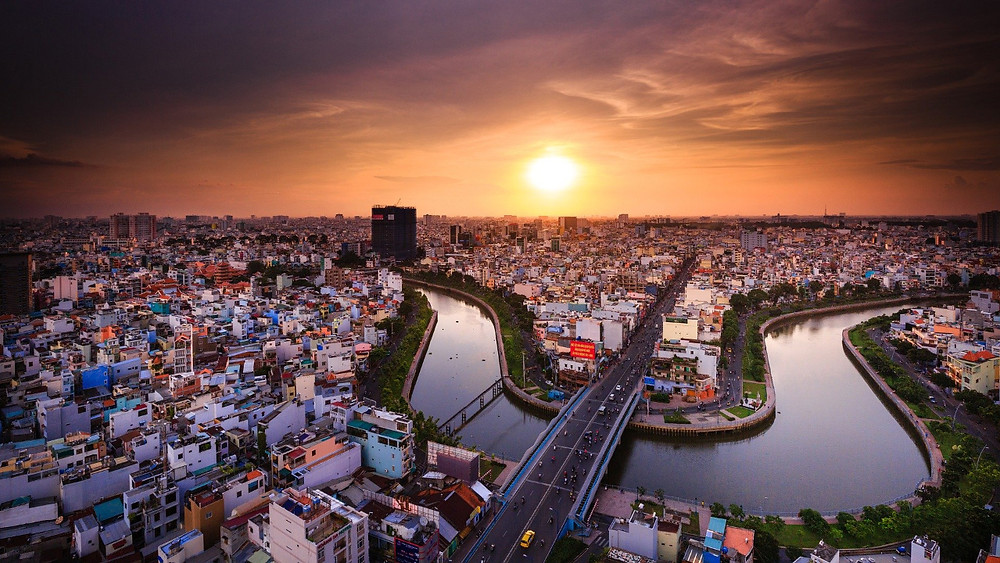 Sun over river and city in Ho Chi Minh, Vietnam