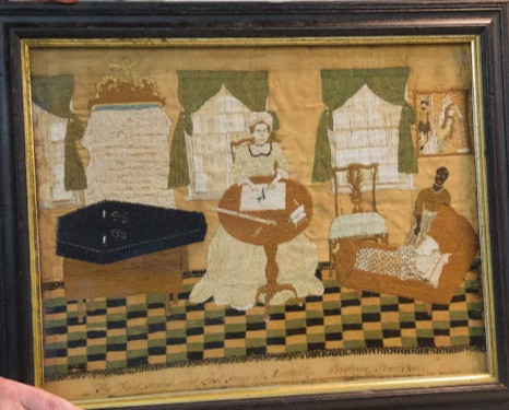 The needlework shows a young enslaved black New England woman with her mistress and charge.