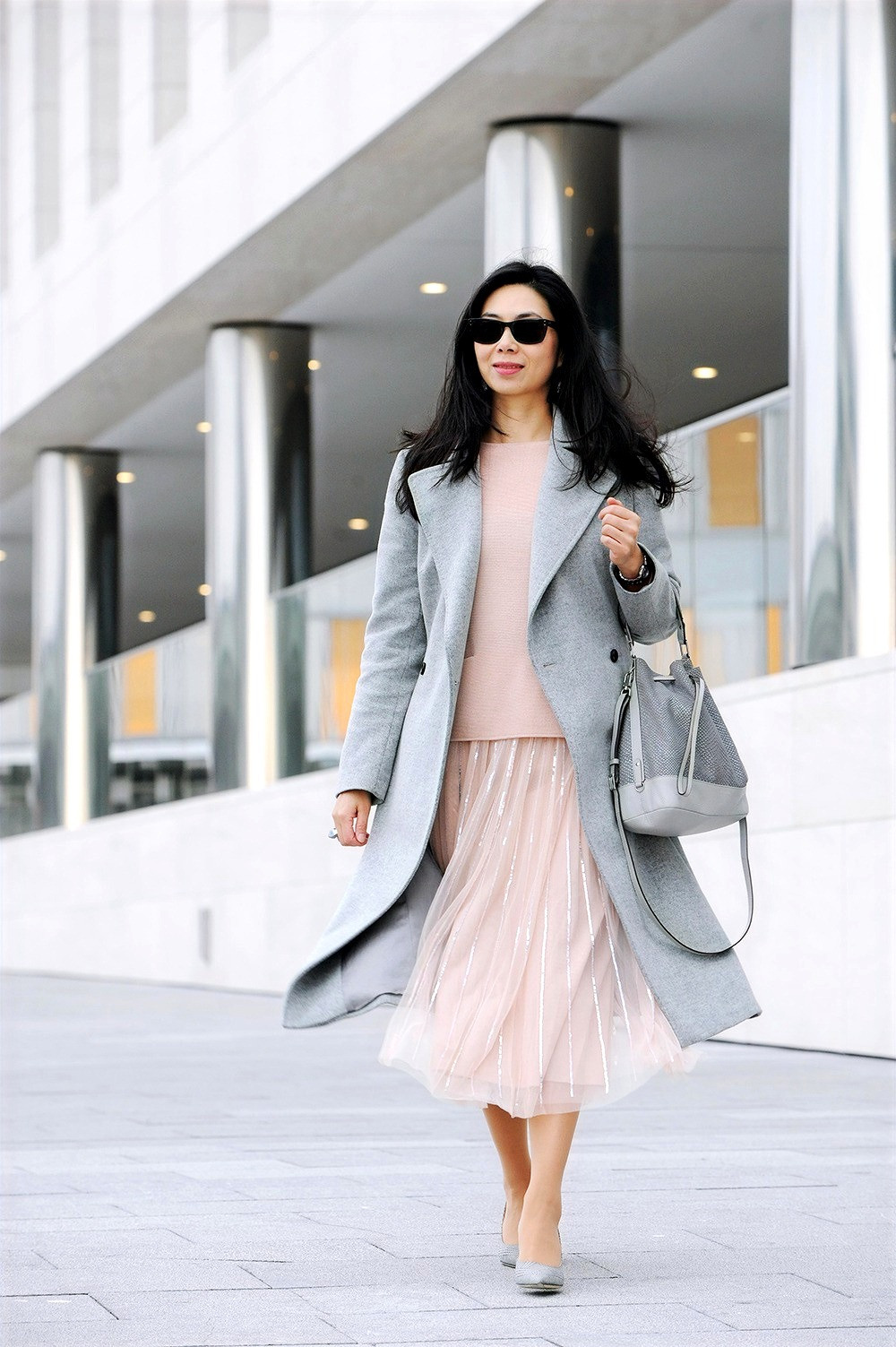 Business casual woman outfit with rose quartz tulle skirt from Needle & Thread and light grey wool coat from Karen Millen.