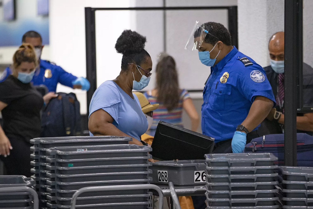 People going through TSA checkpoint in airport.