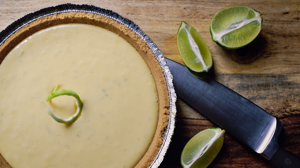A Key lime pie on a chopping block with knife and fresh lime