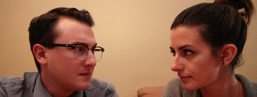 A man and woman stare at each other intensely.