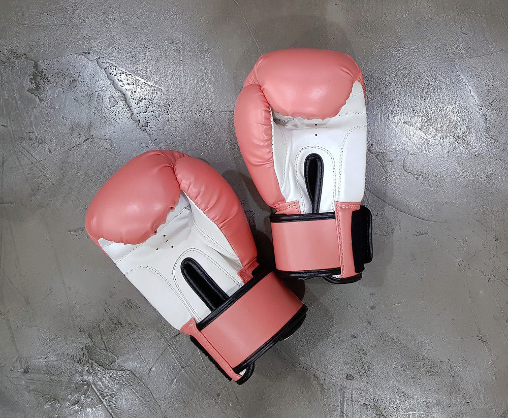 two boxing gloves on concrete surface