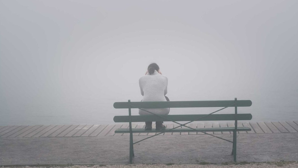 Sad woman sits on a bench alone with her head down before getting treatment for grief in Colorado. At Catalyss Counseling we provide online therapy and in person counseling for grief after loss located in Englewood CO 80209 and 80210