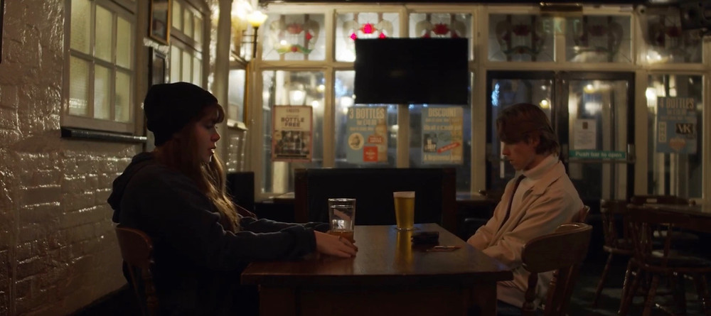 This image shows the two main characters of the short film, Annie (left) and Kyle (right) as they sit at a brown table in a dimly light bar, drinking beer.