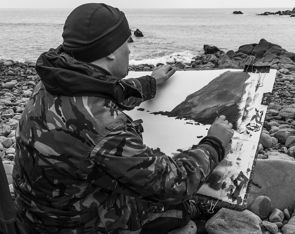 Jonathan Pitts painting plein air on the beach at Duckpool in Cornwall. Jonathan is using watercolours and acrylics.