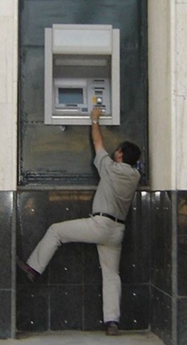 A male tries to use an ATM which is placed too high for his size