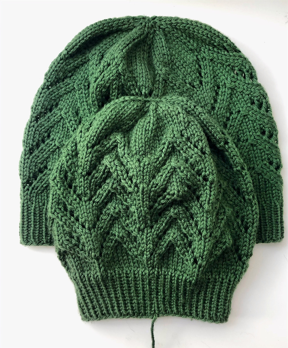 Two green knit hats with lace detail against a white background. One hat is lay on top of the other to show the difference in size and shape as a result of blocking. The one at the back is bigger and wider, the one at the front is smaller and more condensed.