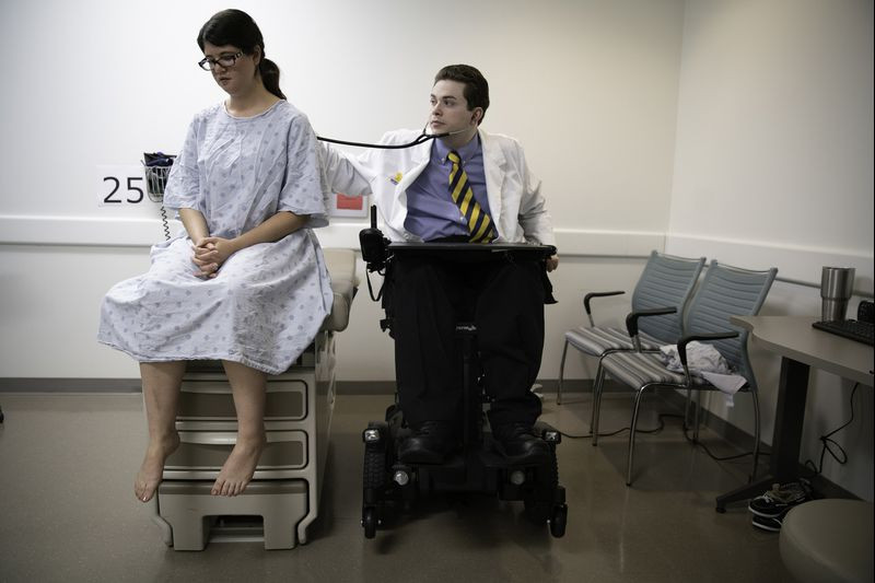 Chris sits in his motorized chair as he examines a patient with a stethoscope.