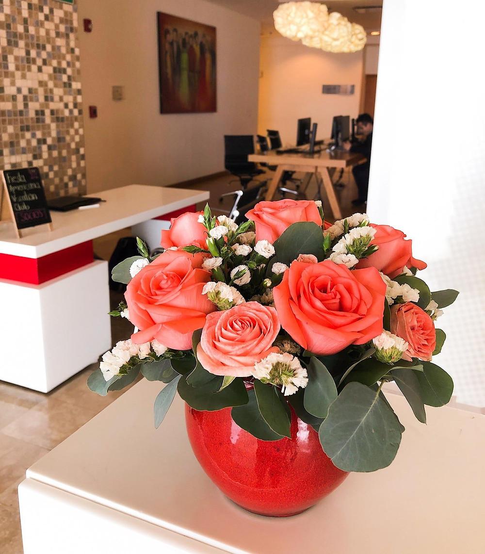Arreglo floral en base roja con rosas naranjas