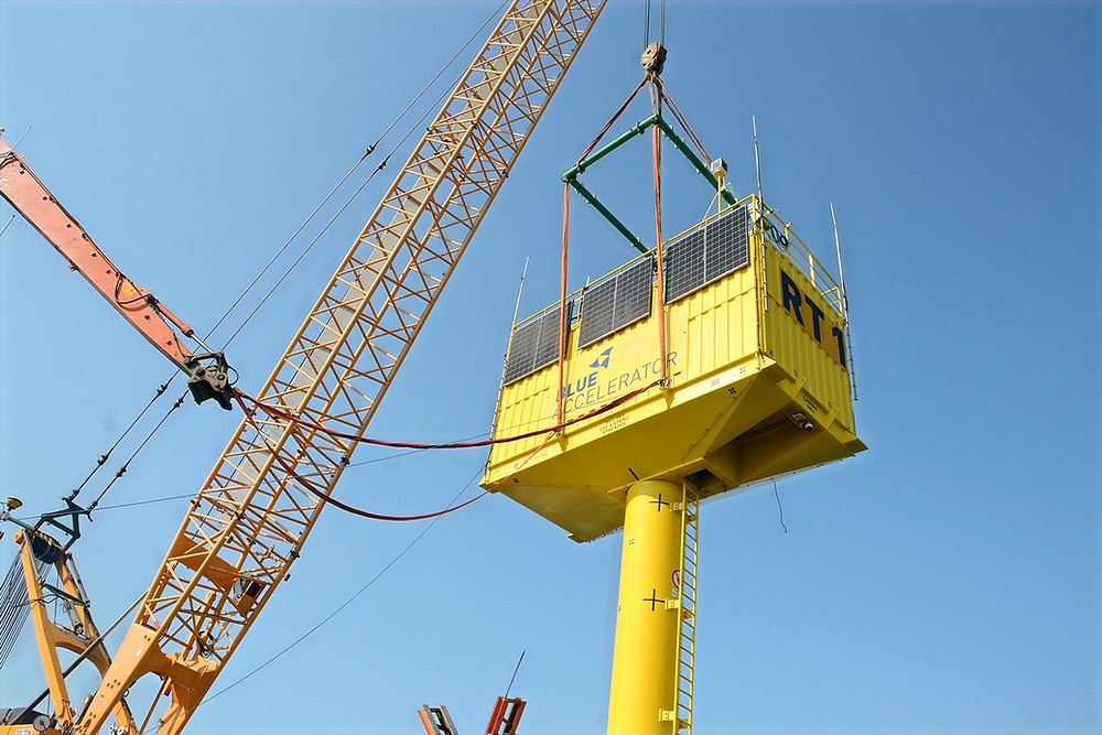 Two cranes are putting the container on the monopile.