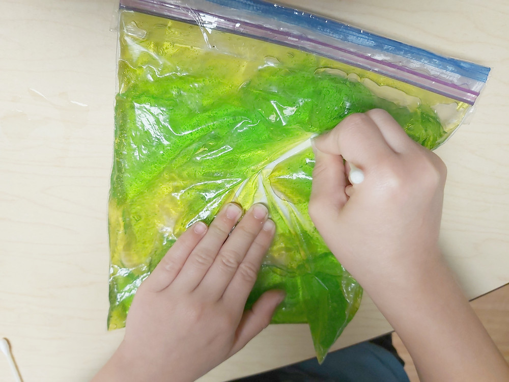 preschooler writing letters and numbers using green sensory bag