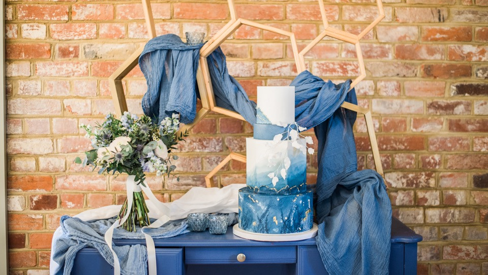 Blue Wedding Cake on Dresser with Hexagon Backdrop Shelving and Cheesecloth Draping