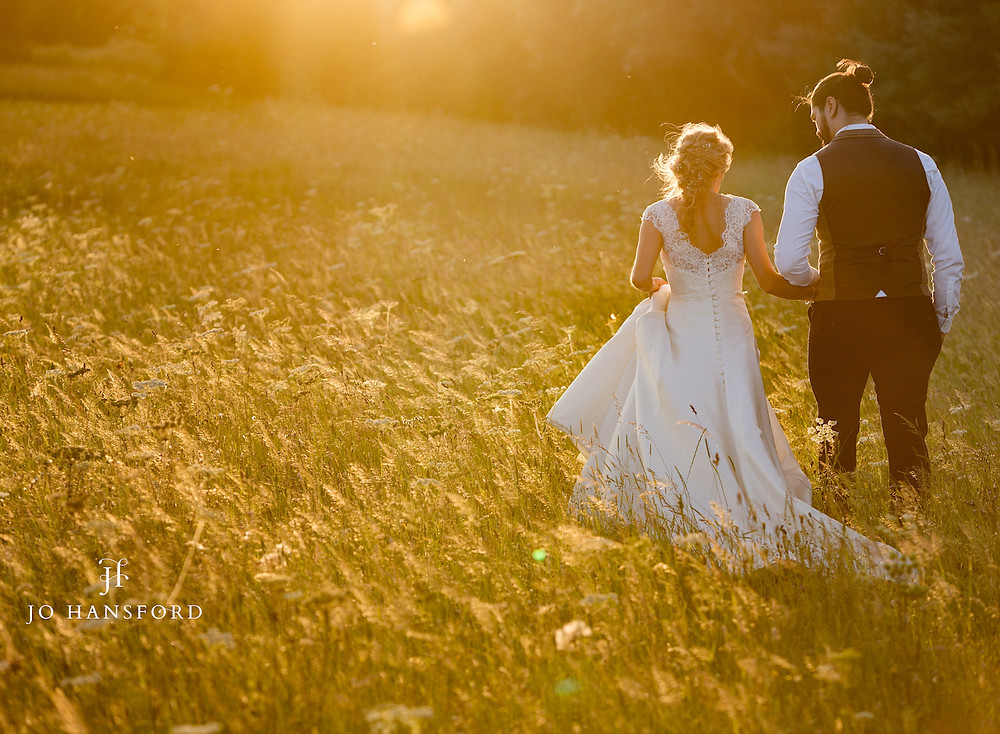 Bride and groom walking through field photo by Jo Hansford Photography