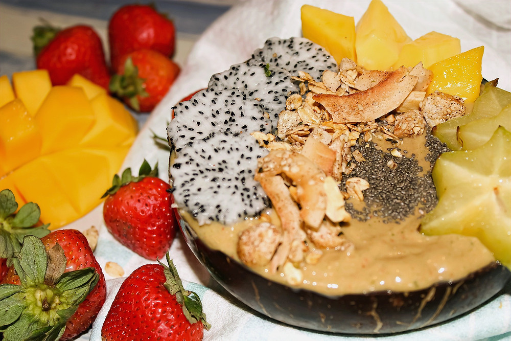 Smoothie bowl made with pineapple mango and passionfruit topped with dragonfruit and star fruit