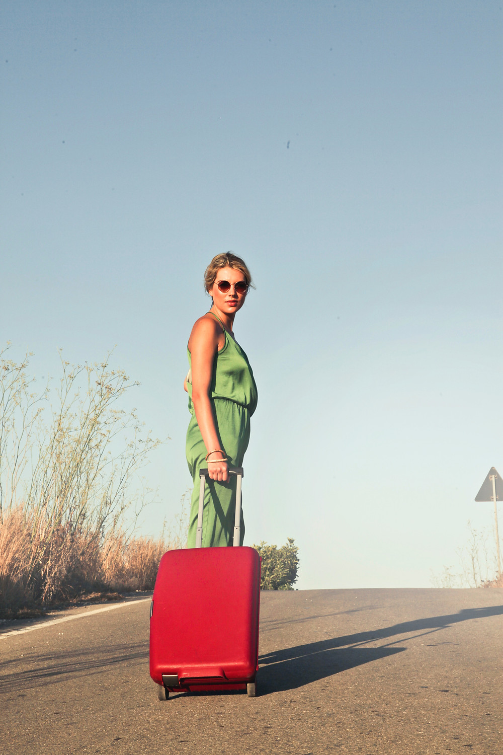 Woman in the middle of the road with a suitcase