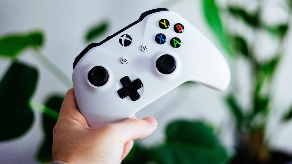 A hand gripping an Xbox Controller behind a white wall and potted plants