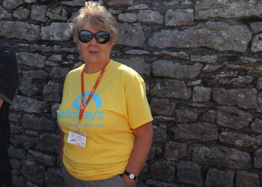Alison is wearing a yellow Galloway's Morecambe Bay Walk T-shirt and her identfication lanyard. She is stood by a stone wall and is wearing sunglasses