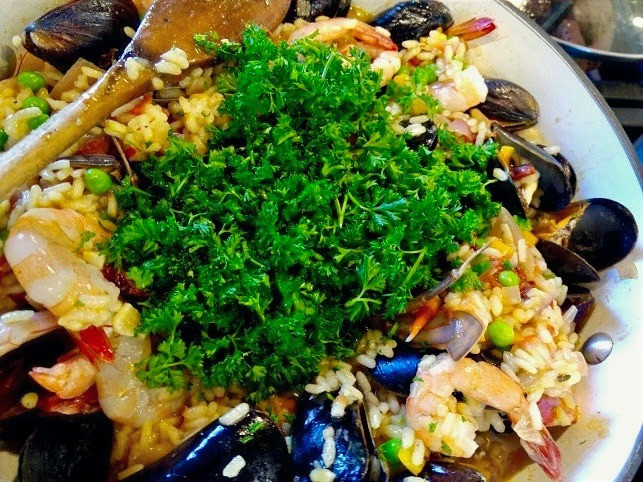 Fresh-cooked paella with shrimp and oysters garnished with parsley