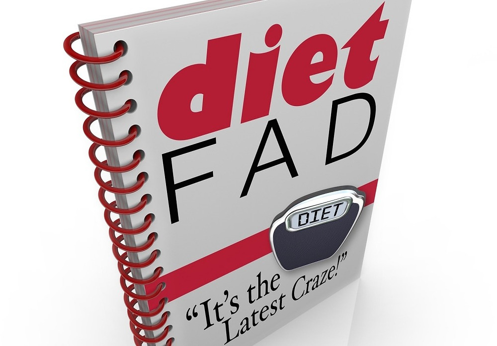 A spiral-bound book with the words Diet Fad - It's the Latest Craze to illustrate a new dieting sens