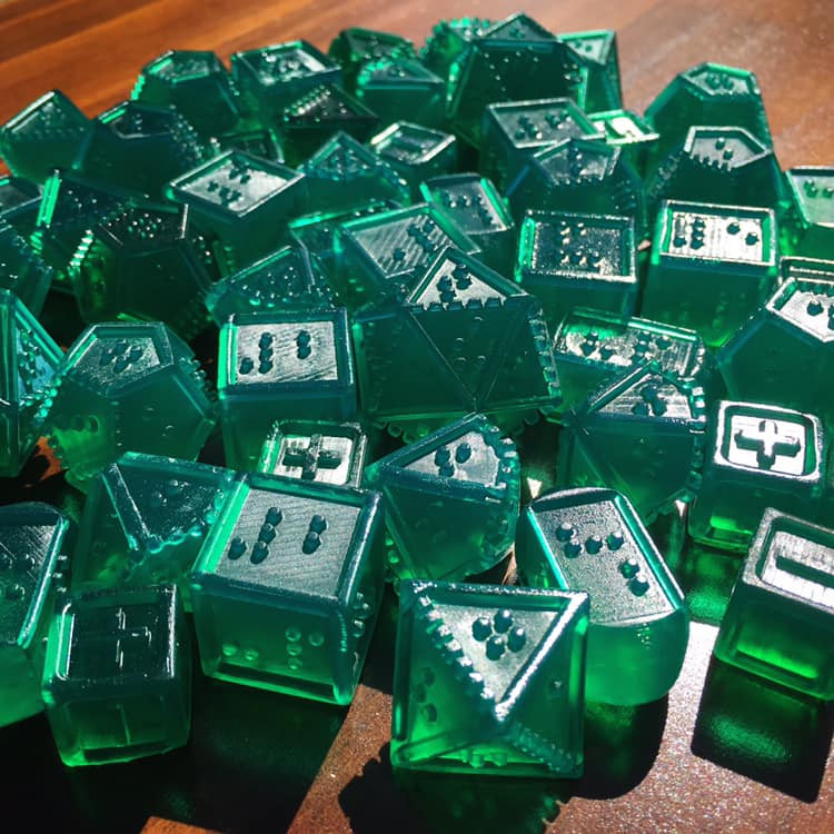 50+ translucent green dice in bright sunlight. Green shadows fall on the table from light passing through dice