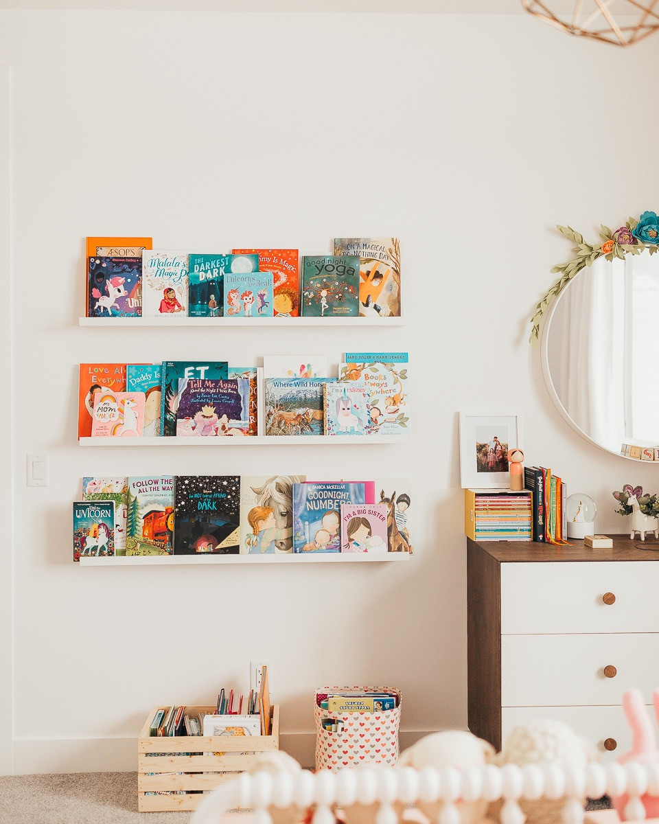 A bookshelf in a little girls room made of picture ledges