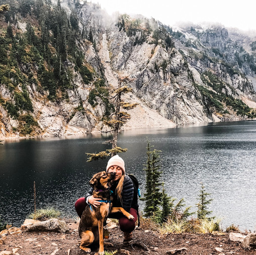 A girl and her dog pose in front of Snow Lake in Washington