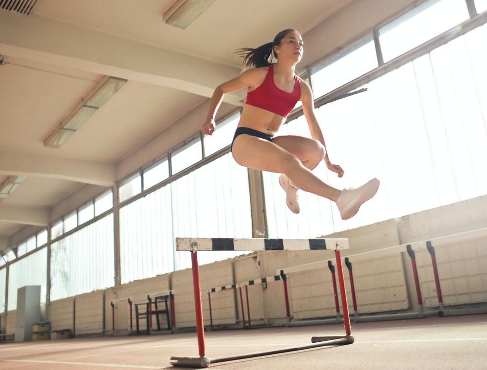 Hürdenläuferin mit weißen Schuhe, schwarzer Shorts und rotem Top spring über eine Hürde. Lokation: Leichtathletikhalle.