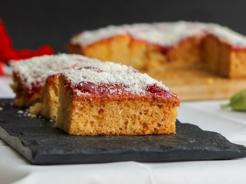 It is a very easy cake recipe prepared with no fancy equipment. This cake consists of a vanilla base drizzled with honey syrup and topped with jam and coconut. This flavoured cake is hugely popular in south India.