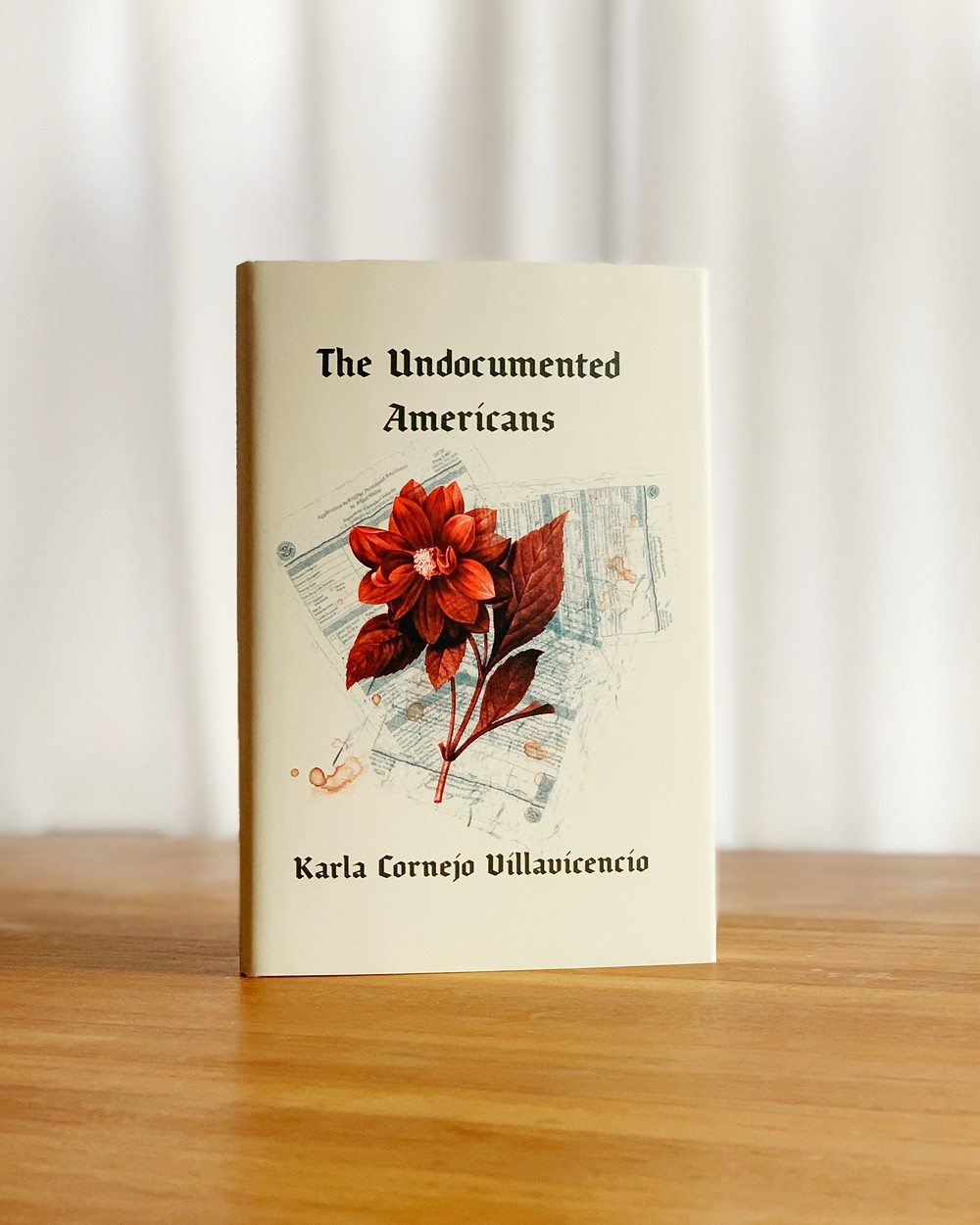 "The book ""The Undocumented Americans"" stands on top of a wood tabletop with a white curtain background."