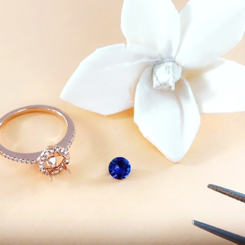 round cut purple sapphire on a peach background next to a dry white flower rose gold semi mount ring and tweezers