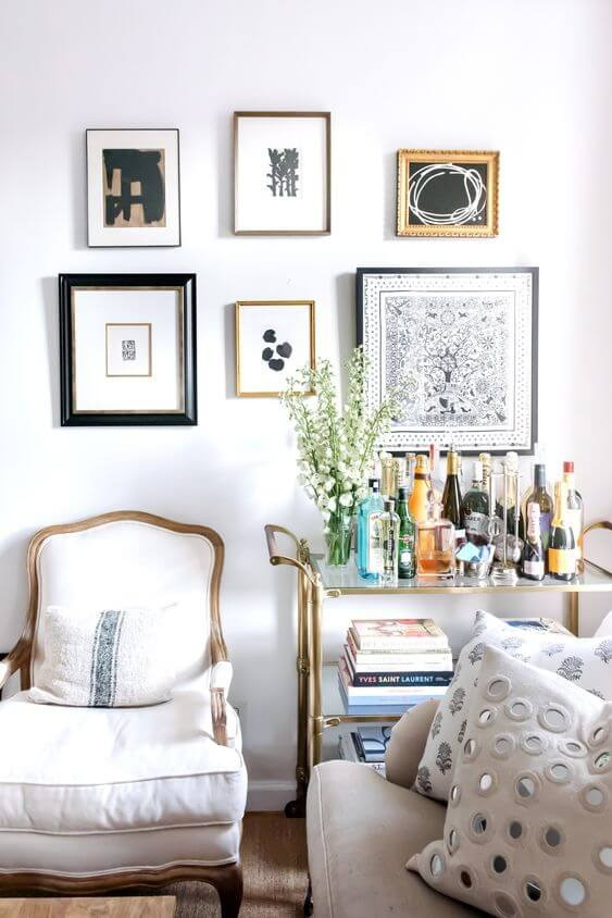 A photo of the corner of a room. Five different-sizes paintings hang on a white wall with black and white abstract prints. The frames are various thicknesses and coloured in black, gold and bronze. A white lounge chair sits against the wall. A cream lounge is on the right with two cream pillows. A wheeled side table sits in the corner. It is gold with glass selves. A vase with green plants sits amongst various alcoholic bottles on the top shelf, a stack of books is on the second shelf