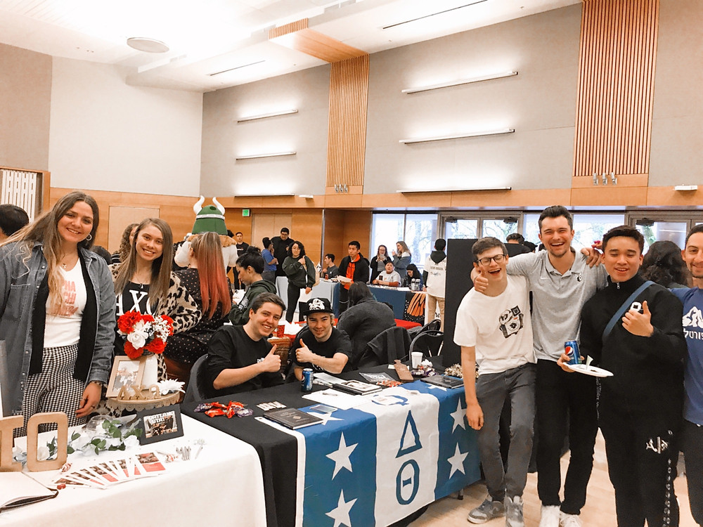 A group of girls stands next to a group of guys, posing for a picture. The girls are in front of an Alpha Chi table, and the boys are in front of a Phi Delt table.