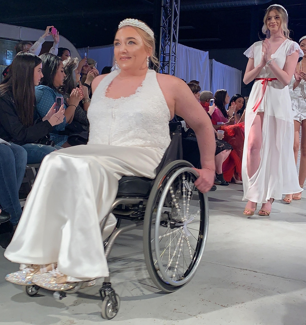 Kate Nelson, Adaptive Model is a white female with blonde hair and uses a wheelchair. She is wheeling down the runway of Denver Fashion Week 2019 in a stunning sleeveless bridal gown and pearl tiara.