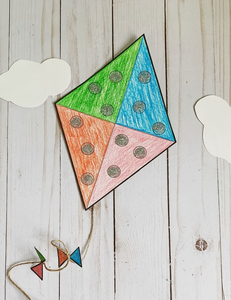 Image of a paper kite in the shape of a diamond with a green, blue, orange and pink quadrant and black circles coloured by crayon. Laying on a wood floor with two white cutouts of clouds nearby.