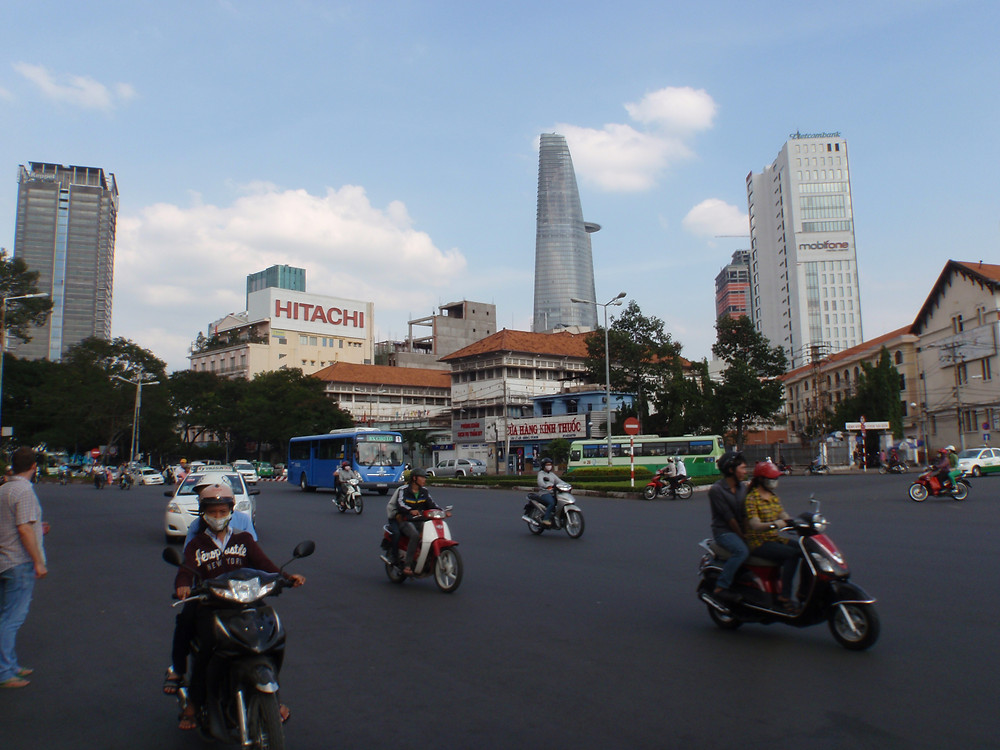 motorcycles pass a roundabout in Ho Chi Minh, the Bitexco Tower in the background