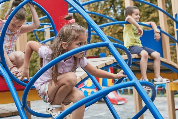 Три деца, две девојчиња и едно момче се играат во забавен парк