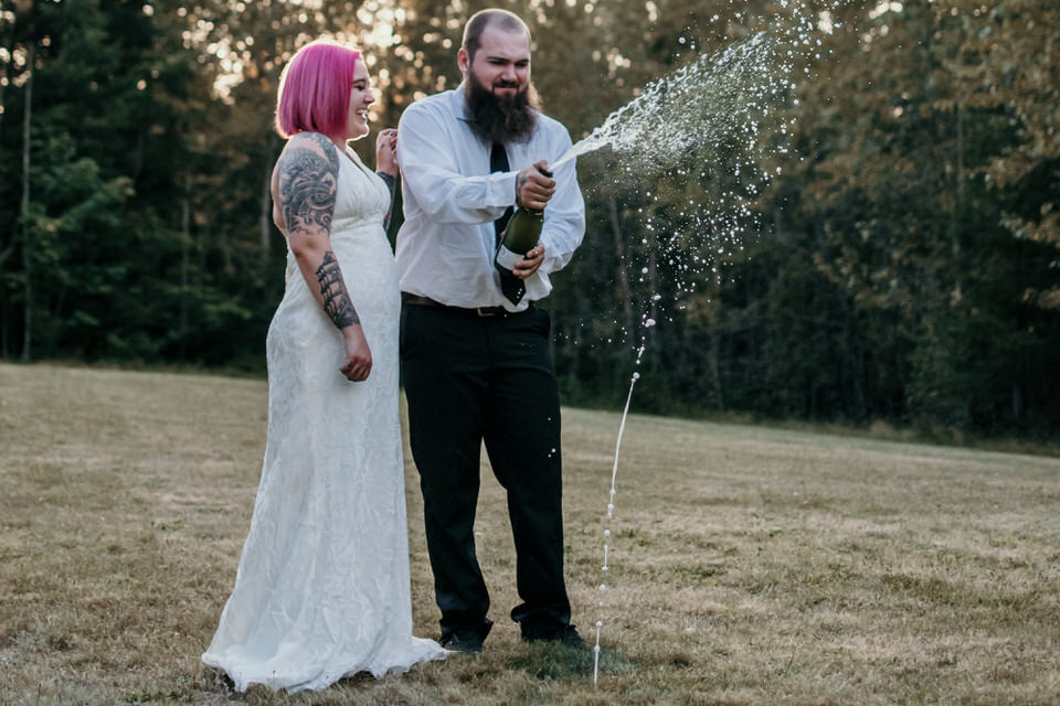 A couple pops champagne on their elopement day in the Snoqualmie National Forest