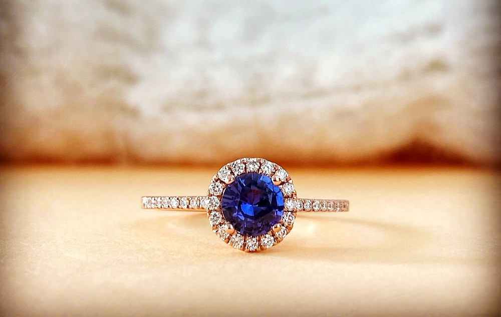 round purple sapphire set in a 14K rose gold ring surrounded by round diamond halo and diamond on shoulders on peach and white background by Tsarina Gems