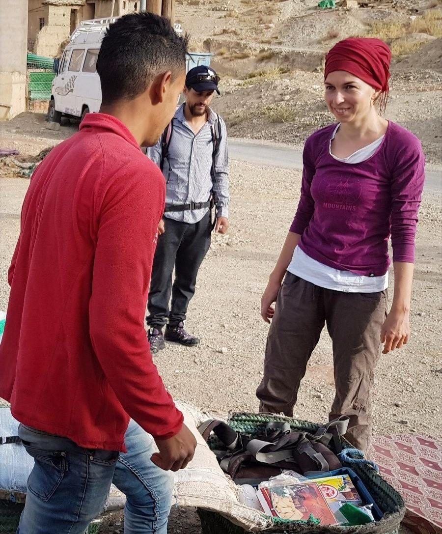 vpravo Tereza Huclova v cervenem turbanu hovori s mladym marocanem v cervene mikine, oba stoji na horske ceste, za nimi bila dodavka
