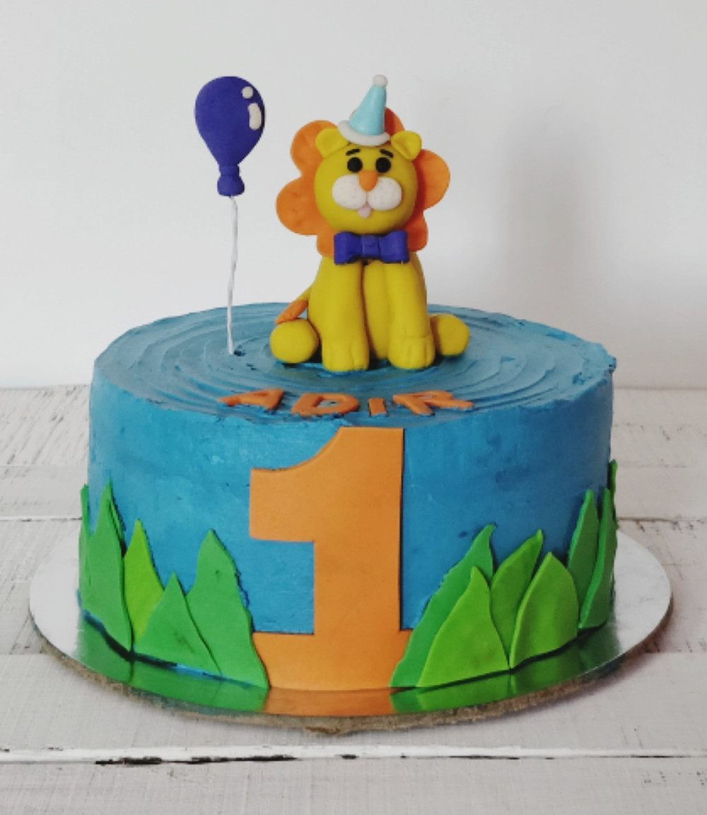 The lion, balloon, grass and name and number are made out of fondant
