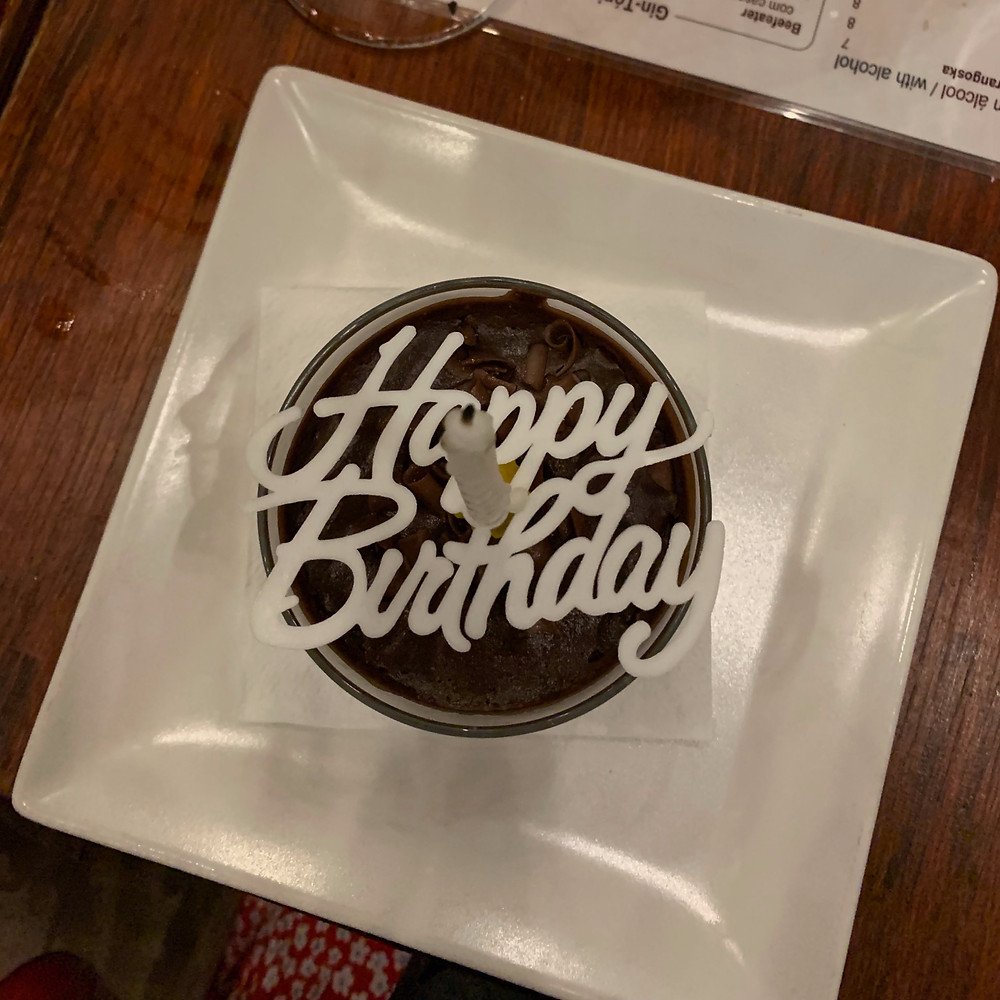 """A white candle over a cursive """"Happy Birthday"""" stencil over a chocolate mousse"""