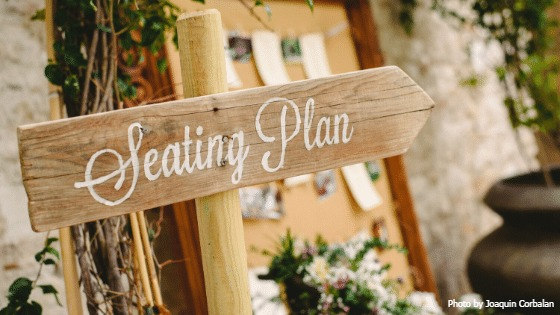 Image of a wedding sign that is a wooden arrow indicating where the seating plan can be found