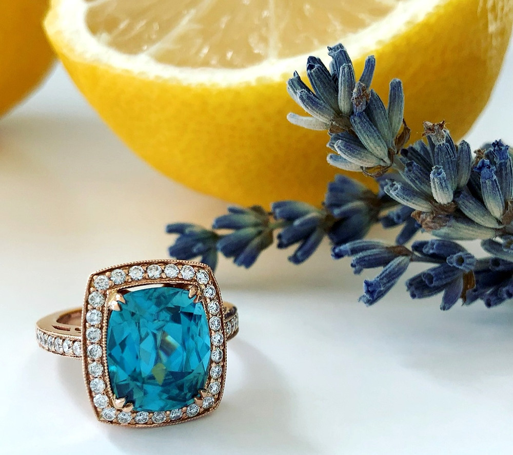 large cushion blue zircon cocktail right hand ring in rose gold with diamond halo and filigree details on white background next to dry lavender and cut up yellow lemon